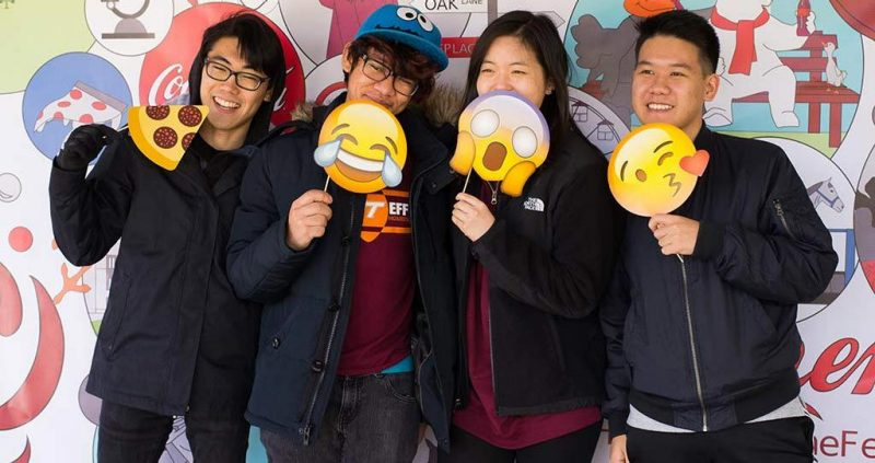 Students holding paper emojiis pose for photos in the Hokies Taste the Feeling booth